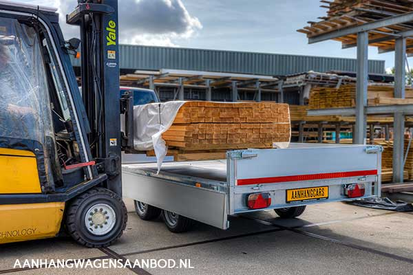 Een plateauwagen wordt door een vorkheftruck via de zijkant beladen met een pak houten balken